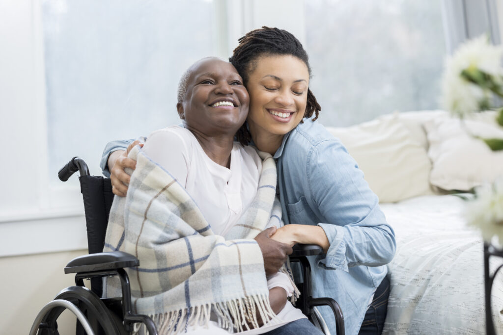 Young woman embraces her beautiful senior mother who is in a wheelchair. The adult daughter is visiting her mom in her mom's home.