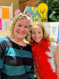 Mother and daughter smiling in front of science project board