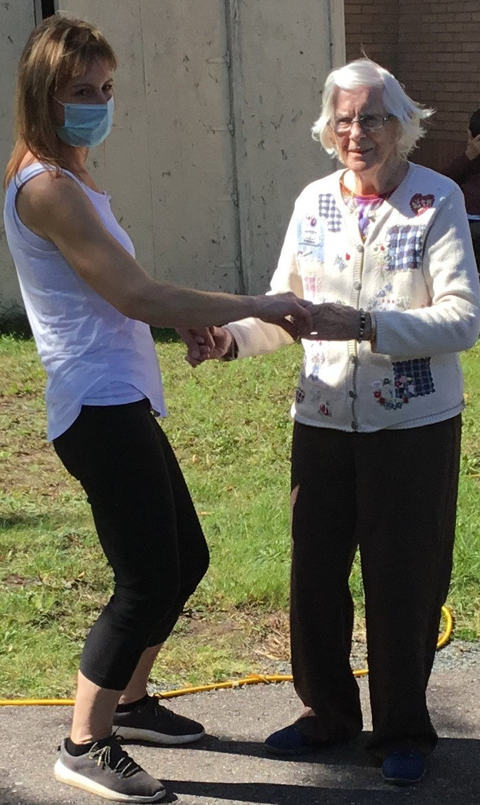 A resident and a team member dancing