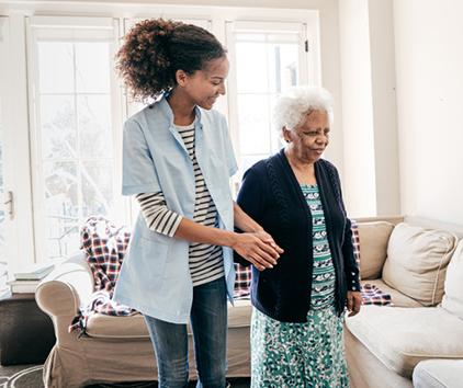 Woman helping an elderly woman walk