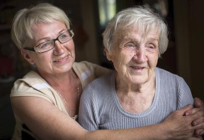 One woman hugging an elderly woman