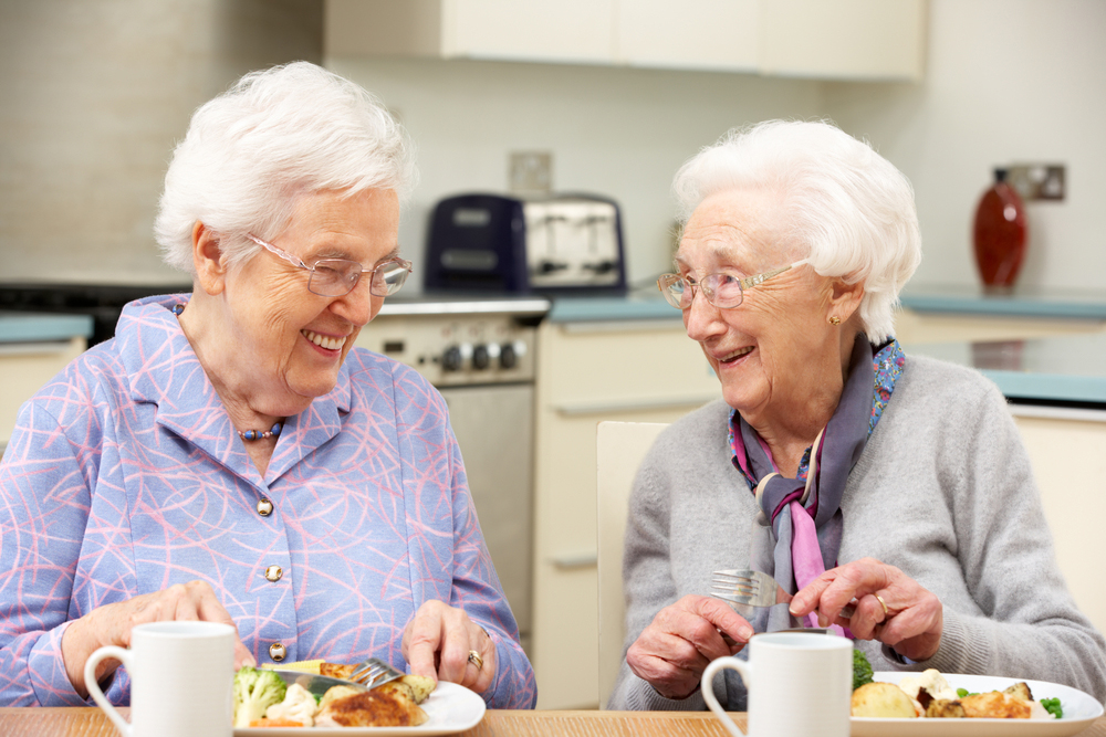two elderly woman eating lunch
