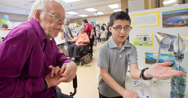Older adults learns about solar panels from a young student