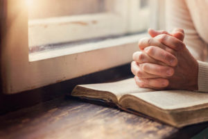 Hands of an unrecognizable woman praying