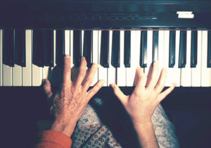 One older hand and one younger hand playing piano