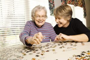 older adult younger adult doing puzzle