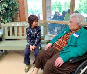 student on elder wisdom bench with resident