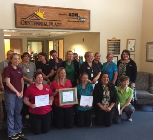 Long-term care home staff smiling holding plaques