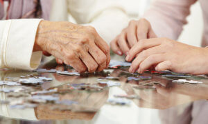 Old hands solving a puzzle