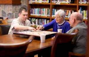 Young man playing a board game with two elderly adults
