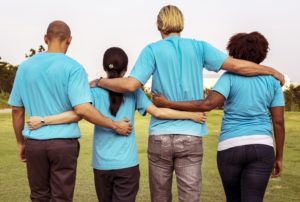 Group of four people holding each other's backs