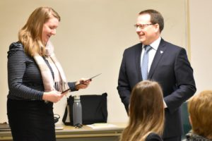 Professor Kate Dupuis, left, looking at certificate from Guelph MPP Mike Schreiner