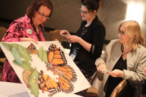 One woman holding a painting of a butterfly while two other woman look at it