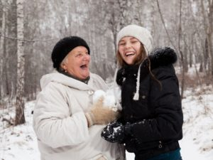Older adult woman and teenage girl smile outside in the forest in winter