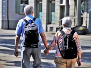 Senior couple walks outdoors, holding hands and wearing backpacks