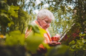 Older woman stands near plants outside