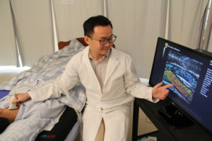 Researcher points to a screen showing results of ultrasound scan while scanning the artery in a test subjects neck