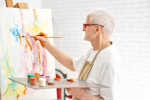 Older man painting on a canvas