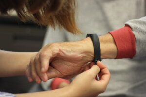 Researcher assists older adult put on a smart watch