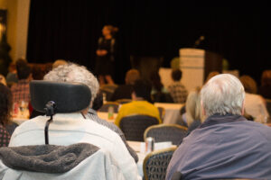 An older woman and man watching a keynote presentation at a Walk with Me conference