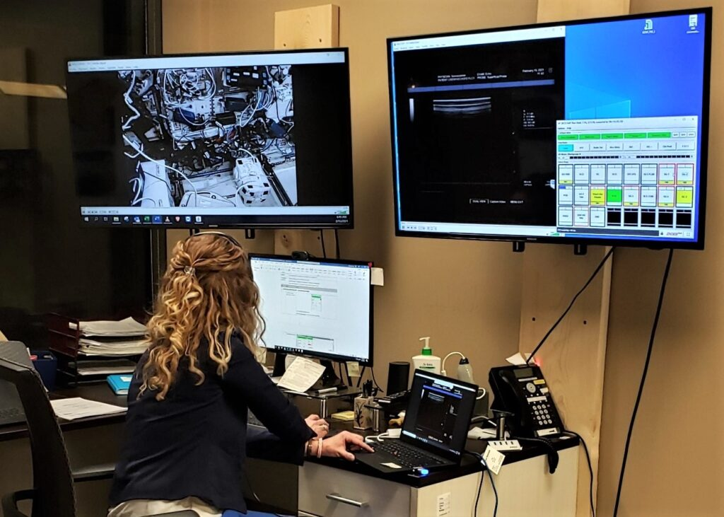 Danielle Greaves sits at a desk and looks at two computer monitors. One shows an image of the inside of the International Space Station, the second screen has readouts from multiple devices.
