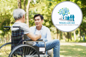 Young man kneels down to talk to older man sitting in wheel chair. Walk With Me Logo is in top left corner