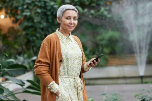 Senior woman stands in garden with cell phone