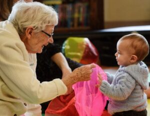 Senior woman hands pink scarf to toddler at a session of the Intergenerational Jamboree music program