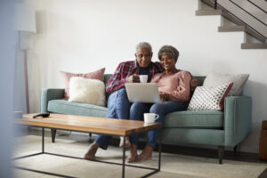 Senior couple sits on couch and use a laptop together