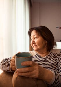 Woman sits and looks out window while holding a mug.